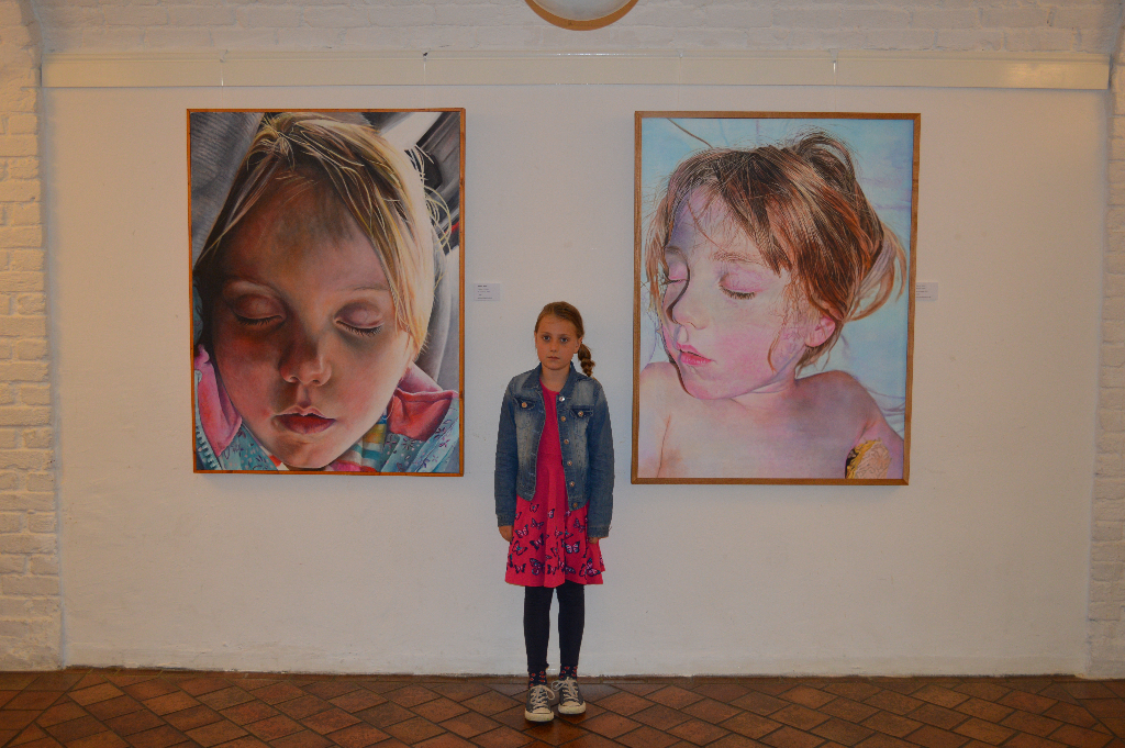 Phoebe in front of a couple of Phoebe paintings